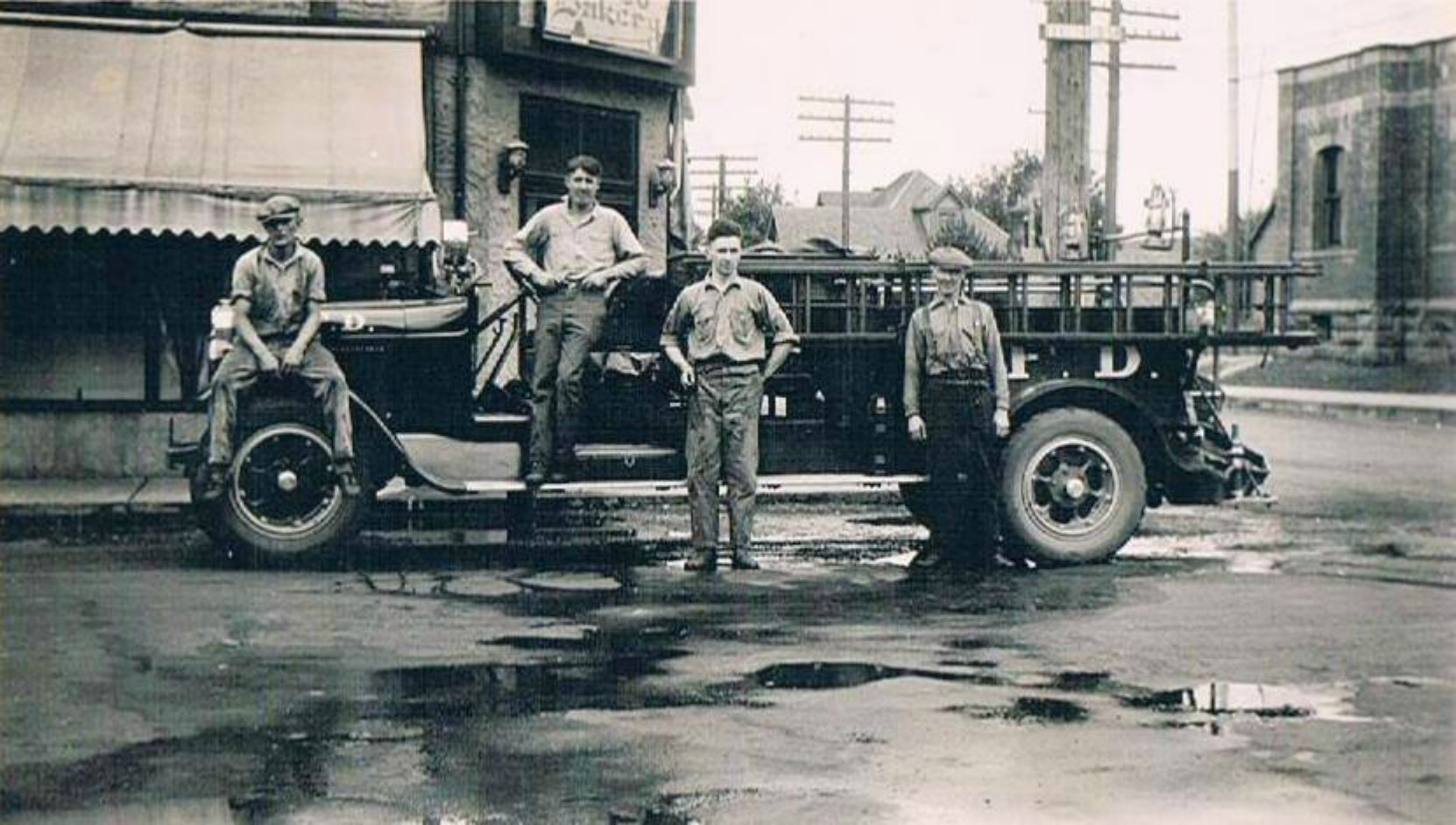 Members of the Duncan Volunteer Fire Department in the summer of 1929 on Kenneth Street at the Craig Street intersection.. Left to right: Rupert MacDonald, Claude Green, Melvin Harris, Daniel R. Hattie. The building behind the truck is 211 Craig Street. (photo courtesy of Sylvia J. Dyer - family collection, used with permission)