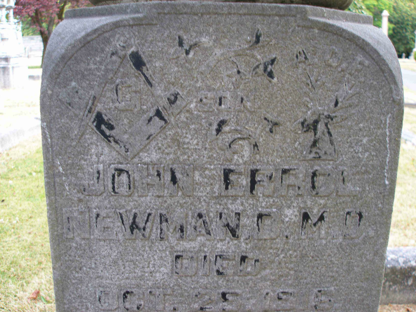 Inscription on the grave of Dr. John Errol Newman in Ross Bay cemetery. Although the original paint is very faded, the raised Masonic Square & Compasses and the Ancient Order of Foresters symbol can still be seen.