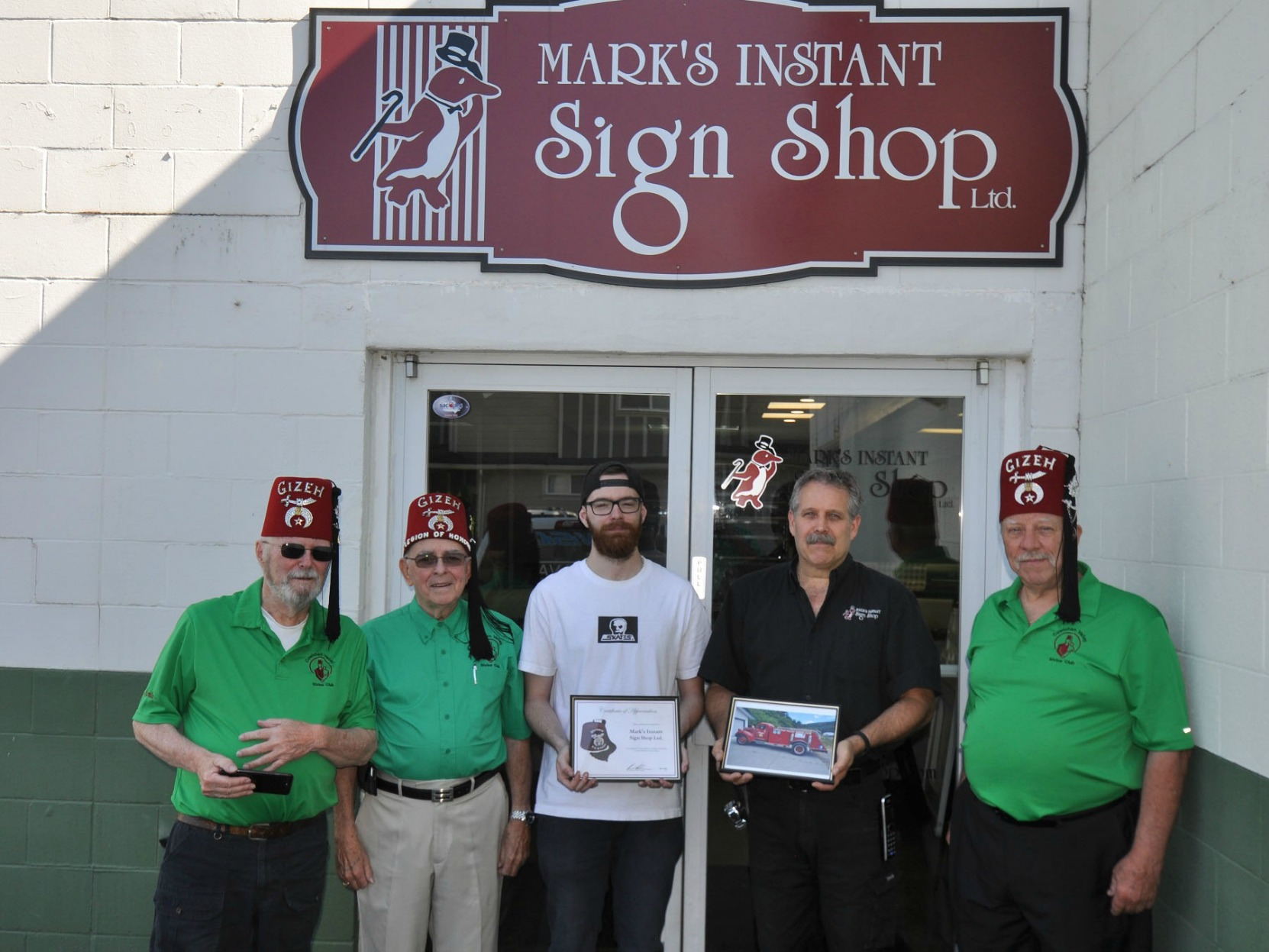 Cowichan valley Shrine Club members Monte Engelson, Brian Nicol and Pat Ffyfe present Certificate of Appreciation to the owners of Mark's Instant Sign Shop, Duncan, B.C. on 26 July 2017 (photo by Cowichan Valley Shrine Club)
