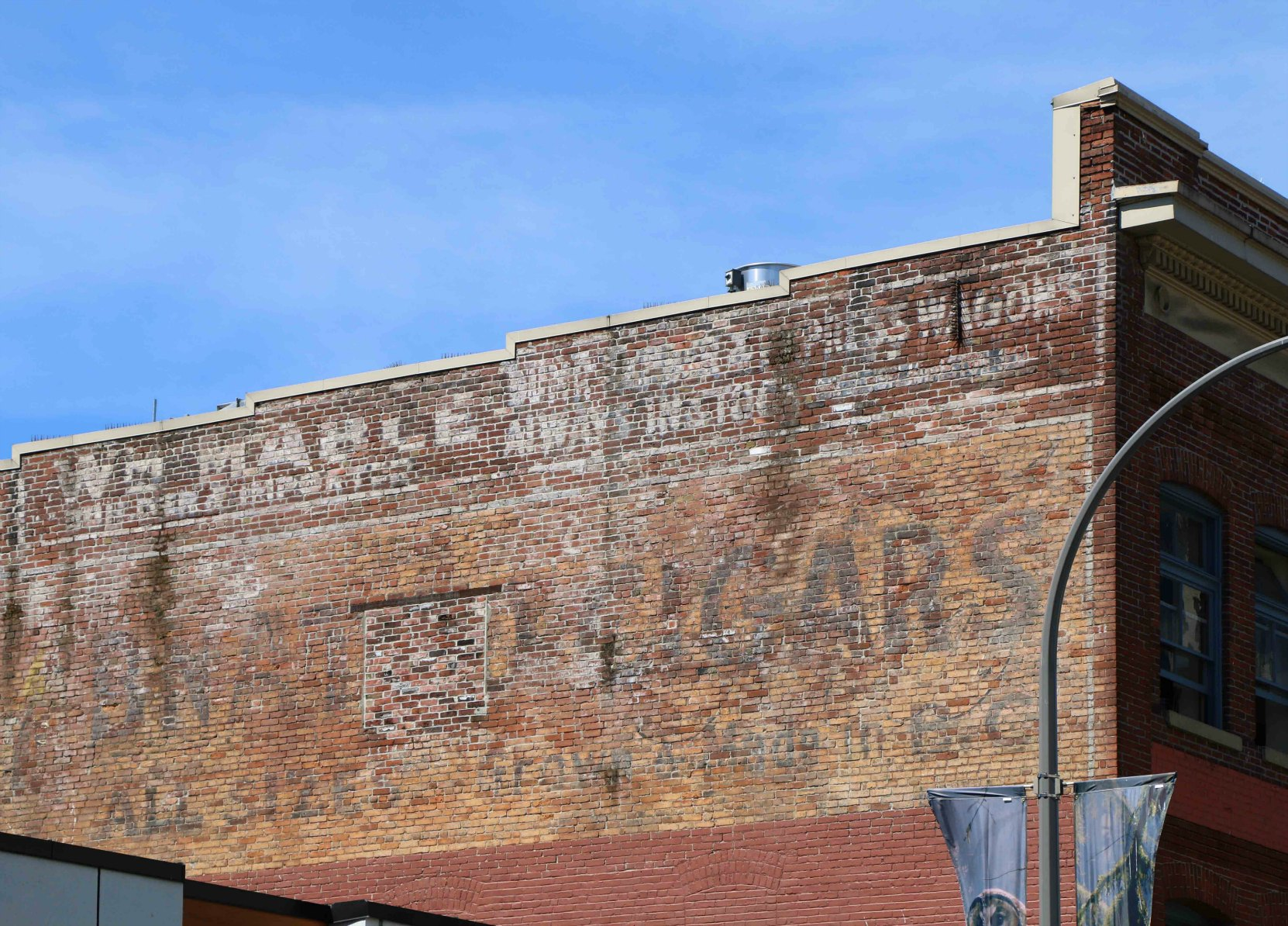 Signs for William Mable's carriage making business are still visible on the east wall of 713-715 Johnson Street, Victoria, B.C. ,built in 1908 by architects Thomas Hooper and C. Elwood Watkins for carriage maker William James Mable, a member of Victoria-Columbia Lodge No.1 (photo by Temple Lodge No. 33 Historian)